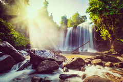 Tropical waterfall. Vintage retro effect filtered hipster style image of tropical waterfall with sun rays in Cambodia