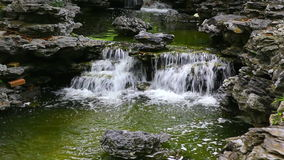 Tropical waterfall in zen garden. Small tropical waterfall in spring garden decorated with taihu or porous stones stock video footage