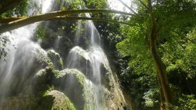 Tropical Waterfalls. Clip from a huge waterfall, with mineral deposit rock formations, in a tropical bamboo forest. Originally taken in 4K resolution and stock video