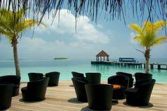 Tropical waters edge bar Maldives. Waters edge cocktail bar Maldives relaxing tropical sun and palms tree shade Royalty Free Stock Photo