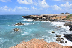 Tropical Waters Off the Shore of Aruba`s Black Stone Beach. Black stone beach with aqua tropical waters in Aruba Stock Photo