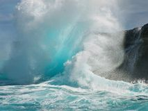Tropical wave creates backwash explosion. Turquoise wave slams into Hawaii's black lava cliffs and turns into a backwash whitewater explosion, backlit by the Stock Photo