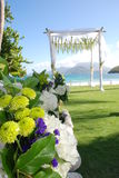 Tropical Wedding sea /beach / ocean with bouquet. Tropical beach and ocean with bamboo poles holding sheer curtains and chairs set up for a wedding Royalty Free Stock Photography