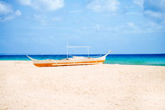 Tropical white sand beach, and fishing boat parked in the sand. Exotic island paradise Royalty Free Stock Photography