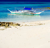 Tropical white sand beach with fishing boat in the water Stock Photo