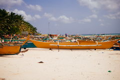 Tropical white sand beach with green palm trees and parked fishing boats in the sand. Exotic island paradise Royalty Free Stock Image