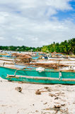 Tropical white sand beach with green palm trees and parked fishing boats in the sand. Exotic island paradise Stock Photography