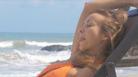Tropical Wind Blows Girl Face in Chair on Beach Close View. Close view soft tropical wind blows up cute girl blond long hair and face in chair on beach against stock video footage