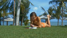 Wind Shakes Girl Long Hair Book Page on Green Lawn. Tropical wind shakes palm branches blonde long hair of girl reading on coast green lawn against azure ocean stock footage