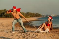 Tropical winter fun. Santa pulling Sexy Santa girl on a sled at the beach.(concept: Tropical winter fun Royalty Free Stock Image
