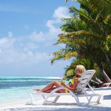Tropical woman on lounge Royalty Free Stock Photo