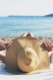 Tropical, woman sunbathing on the beach with hat Royalty Free Stock Photography