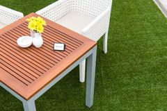 Tropical wooden dinning table on green grass Stock Photo