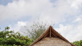 Tropical wooden hut with palm leafs roof on a tropical beach of exotic Bali island, Indonesia. Blue cloudy sky. stock video
