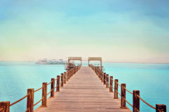 Tropical wooden pier in Red sea. The picture of a tropical wooden pier with yachts in Red sea, Egypt, near Hurghada. Perfect for illustrating travel stories Stock Image