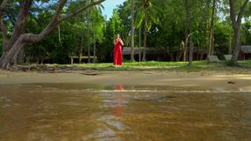 Tropics of Vietnam. Island of Phu Quoc. The woman has a rest on the beautiful island. The woman looks in a distance. On this video you can see as the woman in a stock video footage