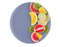 Tropikalna owoc wypełnia prawą połówkę talerz na białym odosobnionym tle na widok fotografia stock