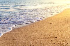 Tropikalna piasek plaża z fala i płonącym słońcem Obraz Stock