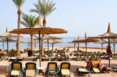 tropikalna plaża na wakacje, tropikalny kurort z słońc łóżkami, słońc loungers i słońce parasole w postaci słomianych kapeluszy p Fotografia Royalty Free