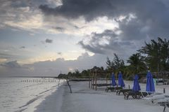 Tropikalna plaża w wschodzie słońca z łóżkami i błękitnymi słońce cieniami chmurzących, słońca, fotografia royalty free