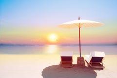 Tropikalna plaża w zmierzchu z plażowymi krzesłami i parasolem fotografia royalty free