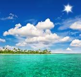 Tropikalna plaża z drzewkami palmowymi i pogodnym niebieskim niebem Fotografia Royalty Free