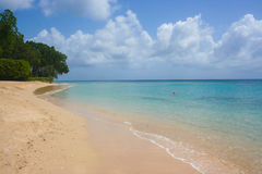 Tropikalna plaża z jasnym morza i koloru żółtego piaskiem Zdjęcia Royalty Free