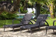 Tropikalna plaża z pływackim basenem, koks drzewka palmowe i rattan daybeds, zbliżamy morze, Bali, Indonezja Obrazy Stock