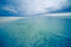 Tropikalna plaża z spokojnym morzem i miękkimi piaskowatymi chmurami plaży i burzowych Obraz Royalty Free