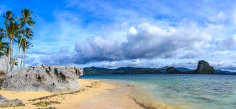 Tropikalna plażowa panorama z niebieskim niebem, chmurami, skałami i palmą, tr Fotografia Royalty Free