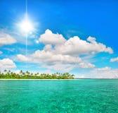 Tropikalna plaża z drzewkami palmowymi i pogodnym niebieskim niebem Zdjęcia Royalty Free