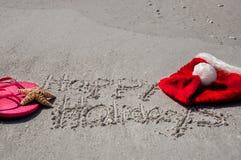 Tropikalni boże narodzenia przy plażą z szczęśliwymi wakacjami pisać wewnątrz, zdjęcia stock