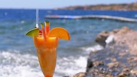 Tropikalny Świeży koktajl w szkle z słomą na plaży Egipt stojaki na skale na tle Czerwony morze zdjęcie wideo