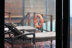 Tropikalny deszcz nad plażowymi desek łóżkami na drewnianej platformie dom na wsi nad wodą Zdjęcia Royalty Free