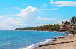 Tropikalny krajobraz z morzem, plażą i drzewkiem palmowym, Piaska plażowy widok z palmami i domem Zdjęcie Royalty Free