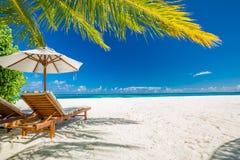 Tropikalny plaża krajobraz, krzesła i parasol pod palmowym liściem na białym piasku blisko morza, zdjęcia stock