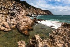 Tropikalny Seascape z Szorstkimi skałami, górami, falą, chmurami i niebem w świetle słonecznym, zdjęcia royalty free