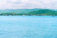 Tropikalny zielony górkowaty wyspa brzeg i błękita spokojny czysty morze Zdjęcie Stock