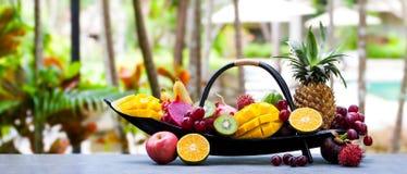 Tropikalnych owoc asortyment w drewnianej ?odzi Plenerowy tropikalny t?o kosmos kopii fotografia royalty free