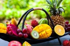 Tropikalnych owoc asortyment w drewnianej ?odzi Plenerowy tropikalny t?o z bliska zdjęcie stock