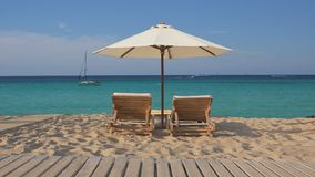 Tropisch exotisch strand met lege houten zitkamer twee sunbeds en witte paraplu stock video
