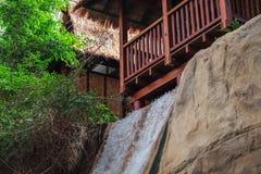 Tropisch huis die zich op een heuvel met een waterval bevinden Bomen op de achtergrond stock fotografie