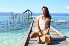 Tropisch meisje op pier met schuilplaats op overzees stock foto's