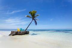 Tropisch paradijsstrand met wit zand, palm en twee ligstoelen Royalty-vrije Stock Afbeelding