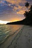 Tropisch strand bij zonsondergang stock foto's