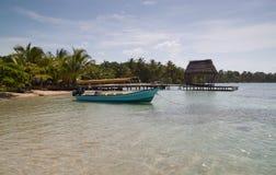 Tropisch strand met boot en dok stock afbeelding