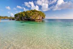 Tropisch strand met een rots in het water, Eiland van Pijnbomen stock afbeelding