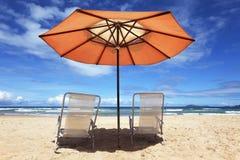 Tropisch strand met parasol Stock Foto