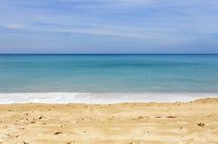 Tropisch zandig strand met blauwe oceaan en blauwe hemelachtergrondafbeelding voor aardachtergrond of de zomerachtergrond royalty-vrije stock foto's