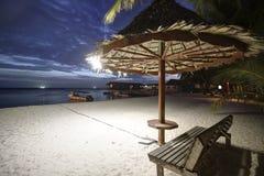 Tropisch zandig strand met palm en bamboehut in zonsondergang Stock Afbeeldingen